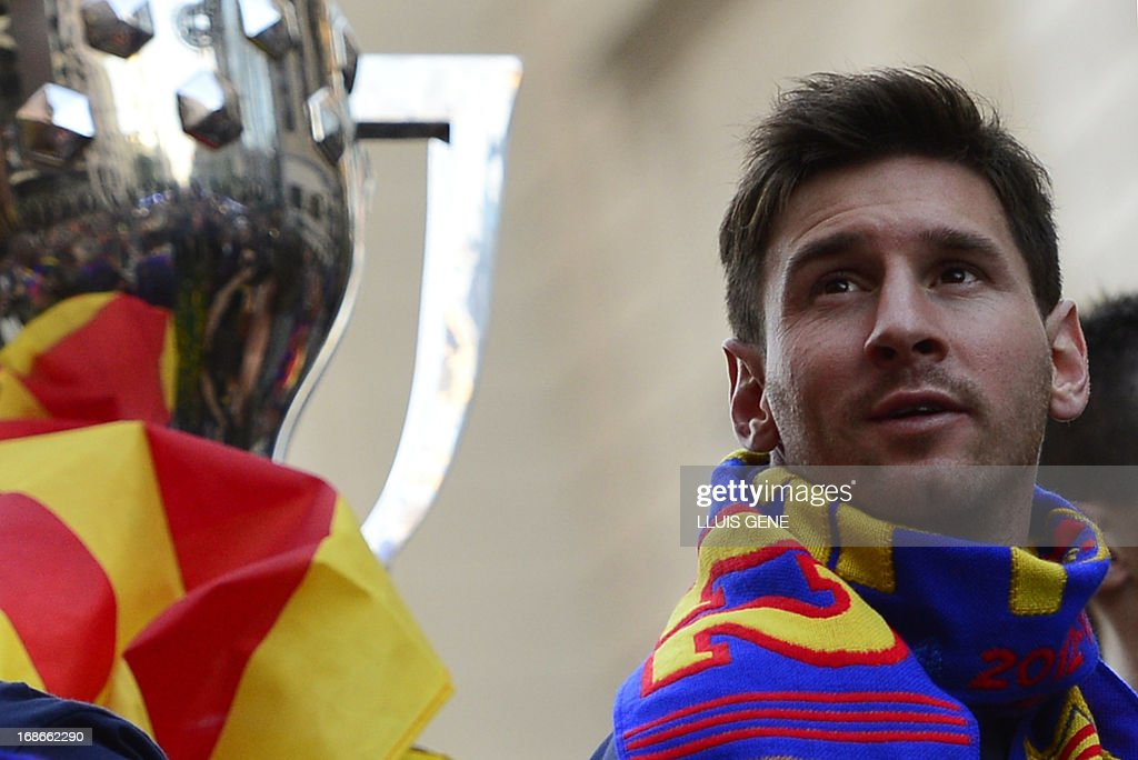 Barcelona's Argentinian forward Lionel Messi (R) reacts as he and his teammates parade on a bus through a crowd of supporters celebrating in the streets of Barcelona on May 13, 2013, two days after their team won the Spanish league. The Catalans didn't even need to set foot on the pitch to seal the title on May 11 as Real Madrid's 1-1 draw with Espanyol meant Barca had already been crowned champions before their 2-1 win over Atletico Madrid on May 12, 2013.