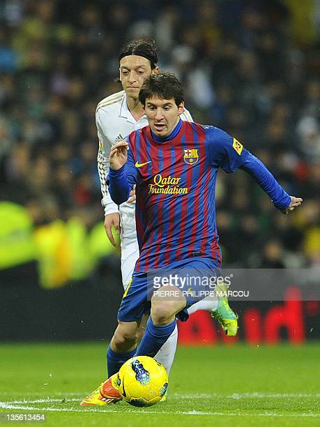 Barcelona's Argentinian forward Lionel Messi runs with the ball during the Spanish league 'El Clasico' football match Real Madrid against Barcelona...