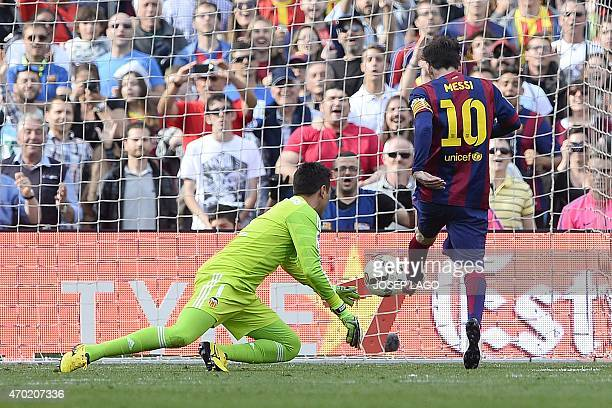 Barcelona's Argentinian forward Lionel Messi scores against Valencia's Brazilian goalkeeper Diego Alves during the Spanish league football match FC...