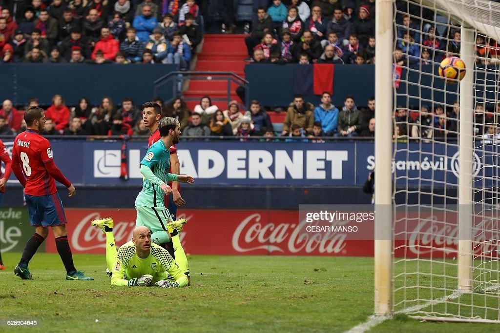 Barcelona's Argentinian forward Lionel Messi scores during the Spanish league football match CA Osasuna vs FC Barcelona at the Reyno de Navarra (El Sadar) stadium in Pamplona on December 10, 2016. / AFP / CESAR