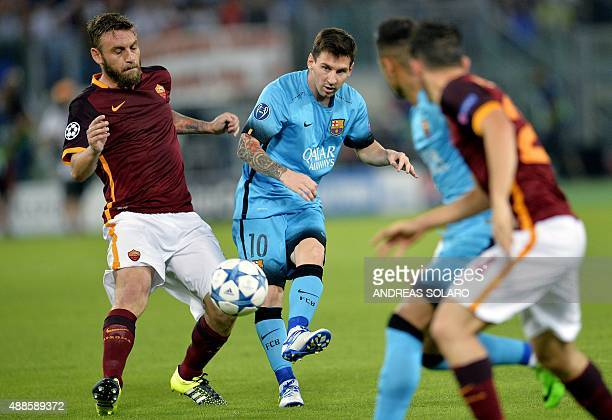 Barcelona's Argentinian forward Lionel Messi shots the ball next to Roma's midfielder from Italy Daniele De Rossi during the UEFA Champions League...