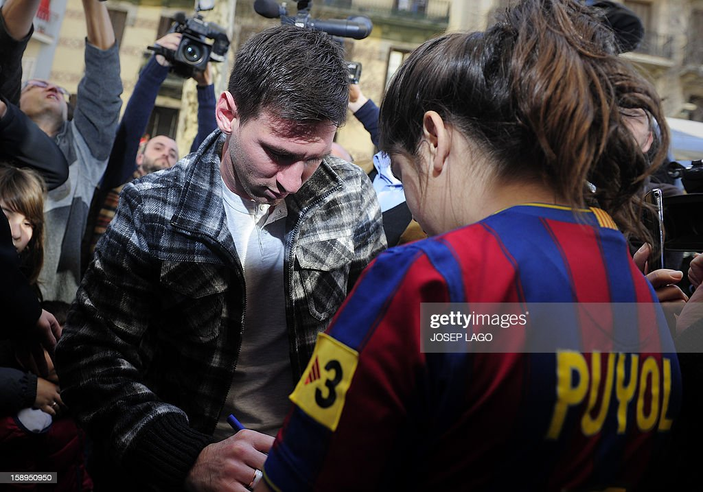 Barcelona's Argentinian forward Lionel Messi (C) signs autographs as he arrives to visit the Hospital de Nens (the Children's Hospital) in Barcelona on January 4, 2013.