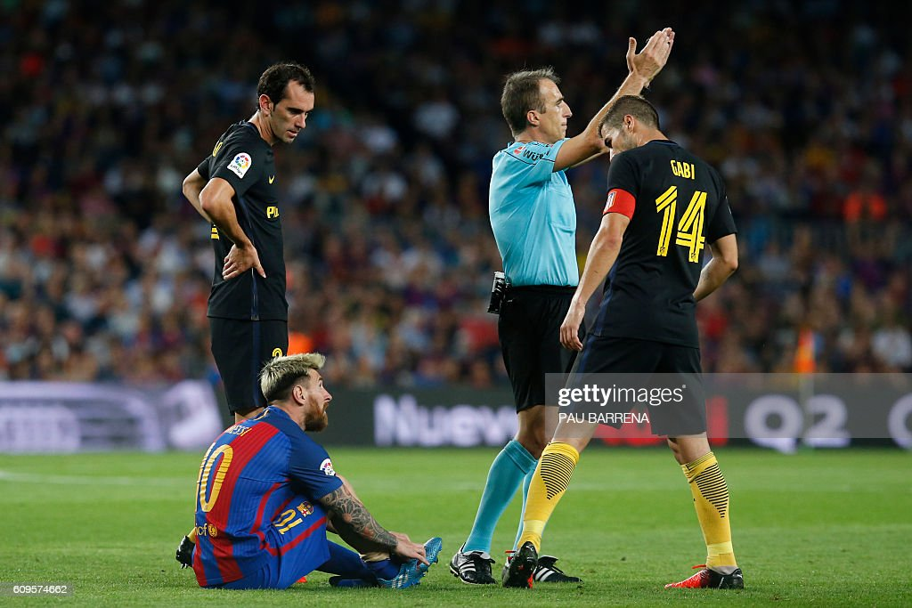 TOPSHOT - Barcelona's Argentinian forward Lionel Messi sits on the ground (L) before leaving the pitch during the Spanish league football match FC Barcelona vs Atletico de Madrid at the Camp Nou stadium in Barcelona on September 21, 2016. / AFP / PAU
