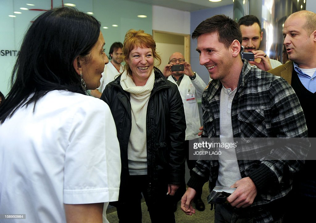 Barcelona's Argentinian forward Lionel Messi (R) smiles during a visit to children and medical staff at the Hospital de Nens (the Children's Hospital) in Barcelona on January 4, 2013. AFP PHOTO / JOSEP LAGO