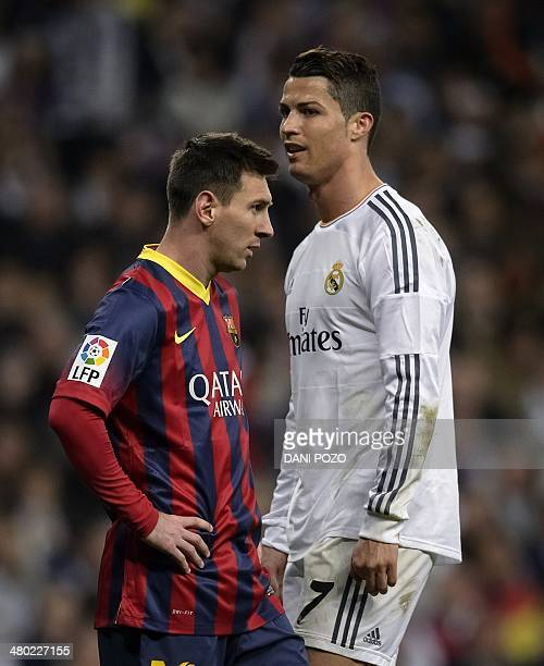 Barcelona's Argentinian forward Lionel Messi stands past Real Madrid's Portuguese forward Cristiano Ronaldo during the 'El clasico' Spanish League...