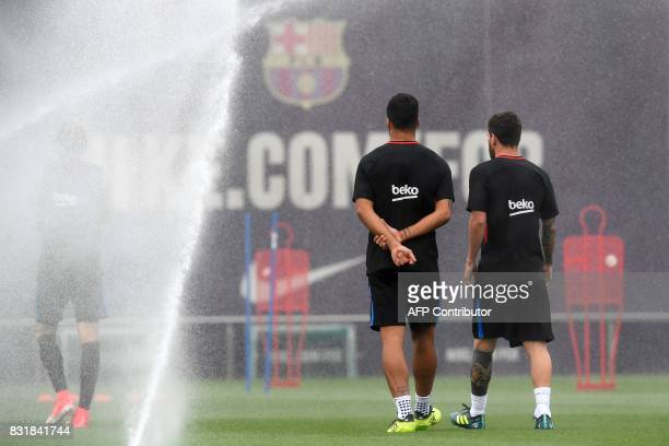 Barcelona's Argentinian forward Lionel Messi talks with Barcelona's Uruguayan forward Luis Suarez during a training session at the Sports Center FC...