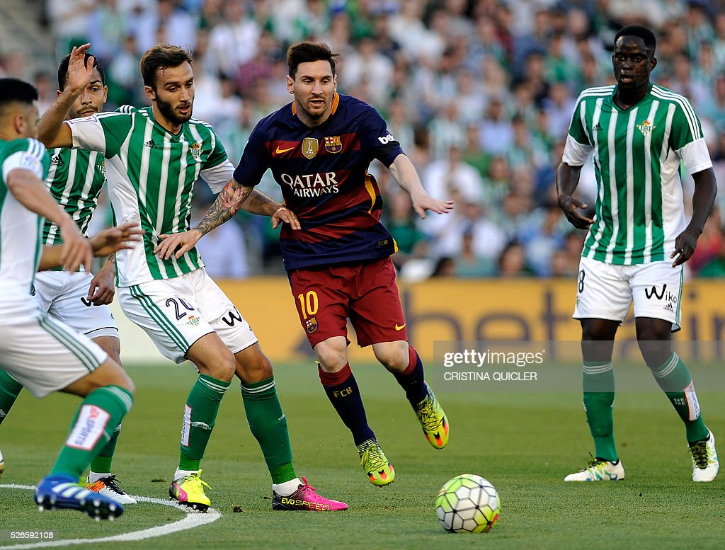 Barcelona's Argentinian forward Lionel Messi (C) ves with Betis' Argentinian defender German Pezzela (L) during the Spanish league football match Real Betis Balompie vs FC Barcelona at the Benito Villamarin stadium in Sevilla on April 30, 2016. / AFP / CRISTINA