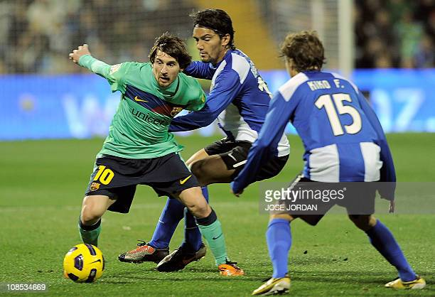 Barcelona's Argentinian forward Lionel Messi vies for the ball with Hercules' defender Kiko Femenia and Hercules' Colombian midfielder Abel Aguilar...