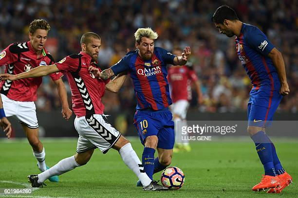 Barcelona's Argentinian forward Lionel Messi vies with Alaves' defender Victor Laguardia beside Barcelona's Uruguayan forward Luis Suarez during the...