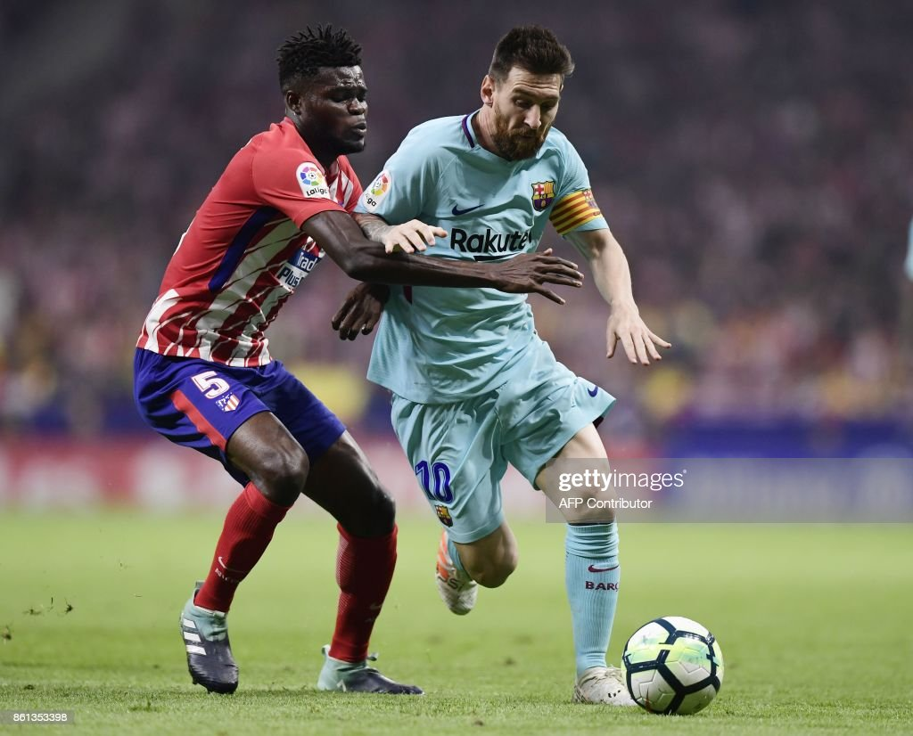 Barcelona's Argentinian forward Lionel Messi (R) vies with Atletico Madrid's Ghanaian midfielder Thomas during the Spanish league football match Club Atletico de Madrid vs FC Barcelona at the Wanda Metropolitano stadium in Madrid on October 14, 2017. /