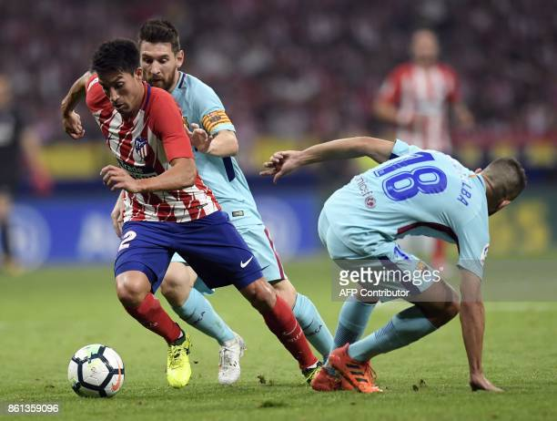 Barcelona's Argentinian forward Lionel Messi vies with Atletico Madrid's Argentinian midfielder Nico Gaitan during the Spanish league football match...