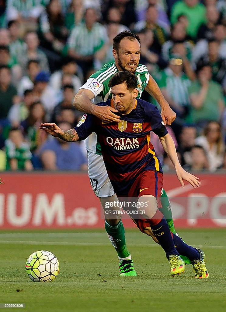 Barcelona's Argentinian forward Lionel Messi (bottom) vies with Betis' German defender Heiko Westermann (top) during the Spanish league football match Real Betis Balompie vs FC Barcelona at the Benito Villamarin stadium in Sevilla on April 30, 2016. / AFP / CRISTINA