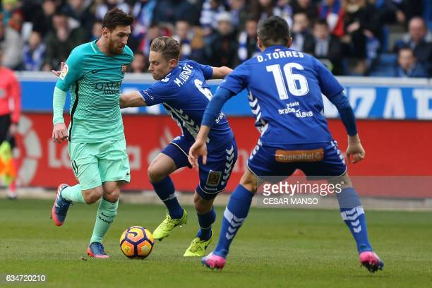 Barcelona's Argentinian forward Lionel Messi vies with Deportivo Alaves midfielder Marcos Llorente during the Spanish league football match Deportivo...