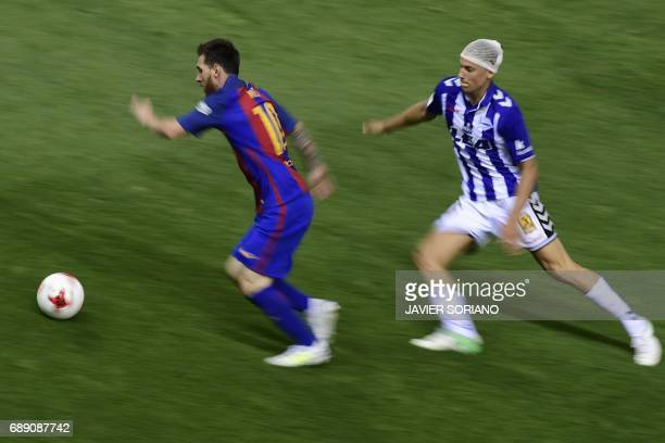 Barcelona's Argentinian forward Lionel Messi vies with Deportivo Alaves' midfielder Marcos Llorente during the Spanish Copa del Rey final football...