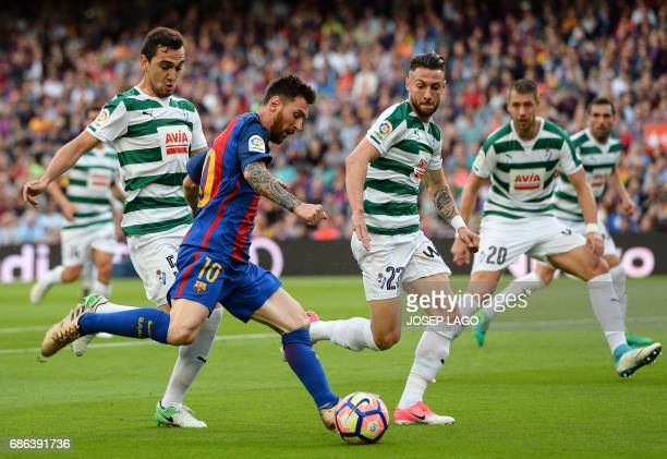 TOPSHOT Barcelona's Argentinian forward Lionel Messi vies with Eibar's Argentinian midfielder Gonzalo Escalante and Eibar's defender David Junca...