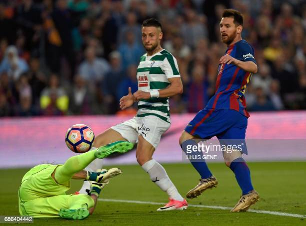 Barcelona's Argentinian forward Lionel Messi vies with Eibar's goalkeeper Yoel Rodriguez during the Spanish league football match FC Barcelona vs SD...