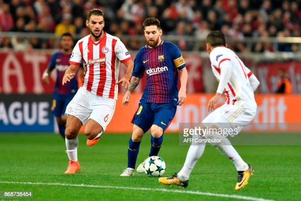Barcelona's Argentinian forward Lionel Messi vies with Olympiakos' midfielder Panagiotis Tachtsidis during the UEFA Champions League group D football...