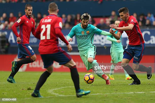 Barcelona's Argentinian forward Lionel Messi vies with Osasuna's defender David Garcia during the Spanish league football match CA Osasuna vs FC...