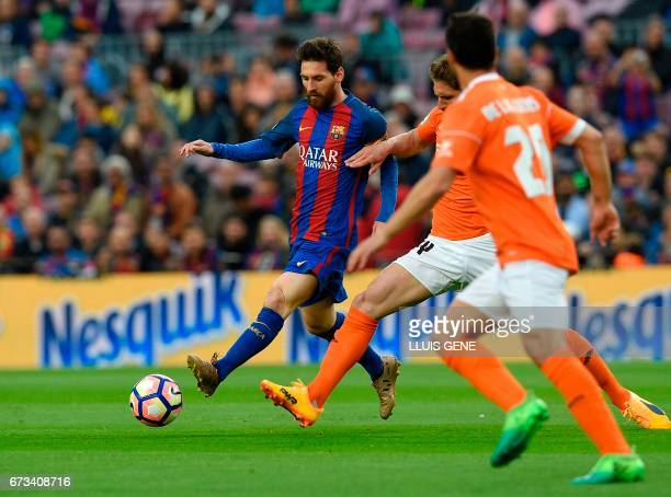 Barcelona's Argentinian forward Lionel Messi vies with Osasuna's midfielder Roberto Torres during the Spanish league football match FC Barcelona vs...