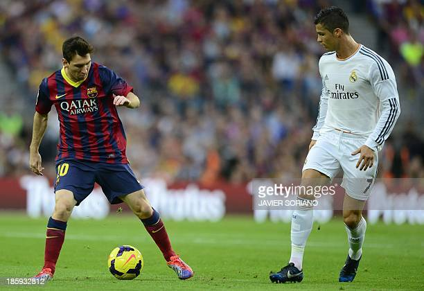 Barcelona's Argentinian forward Lionel Messi vies with Real Madrid's Portuguese forward Cristiano Ronaldo during the Spanish league Clasico football...