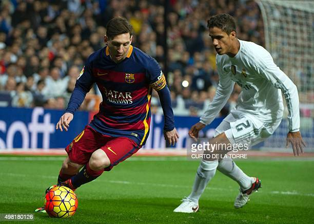 Barcelona's Argentinian forward Lionel Messi vies with Real Madrid's French defender Raphael Varane during the Spanish league 'Clasico' football...
