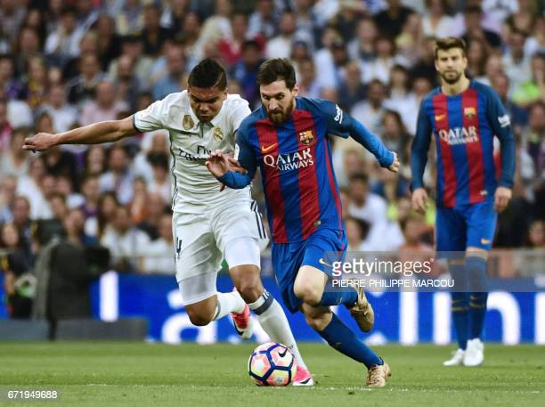 Barcelona's Argentinian forward Lionel Messi vies with Real Madrid's Brazilian midfielder Casemiro during the Spanish league football match Real...