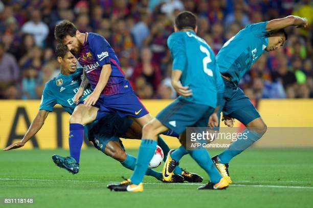Barcelona's Argentinian forward Lionel Messi vies with Real Madrid's French defender Raphael Varane and Real Madrid's Brazilian midfielder Casemiro...