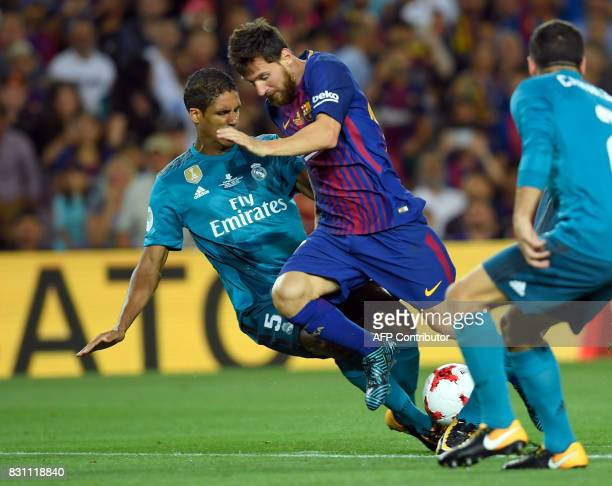 Barcelona's Argentinian forward Lionel Messi vies with Real Madrid's French defender Raphael Varane during the Spanish Supercup first leg football...