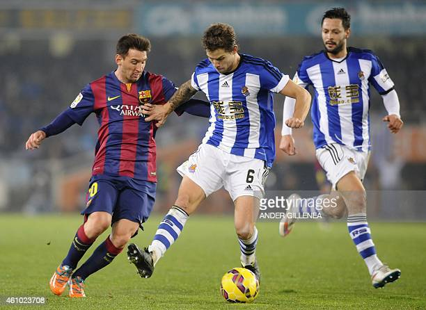 Barcelona's Argentinian forward Lionel Messi vies with Real Sociedad's defender Inigo Martinez during the Spanish league football match Real Sociedad...