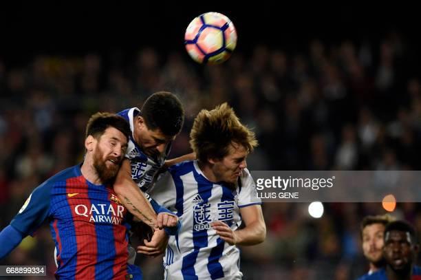Barcelona's Argentinian forward Lionel Messi vies with Real Sociedad's defender Yuri Berchiche and Real Sociedad's defender Bautista during the...
