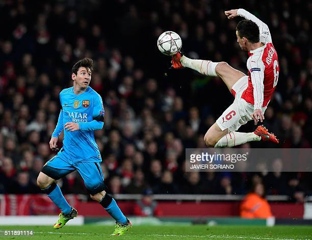 Barcelona's Argentinian forward Lionel Messi watches as Arsenal's French defender Laurent Koscielny jumps to control the ball during the UEFA...