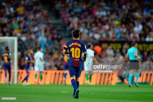 Barcelona's Argentinian forward Lionel Messi wears a black armband for the victims of the Barcelona and Cambrils attack as he walks on the pitch...