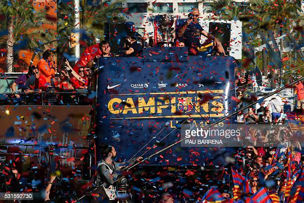 Barcelona's Argentinian midfielder Javier Mascherano takes pictures as he parades with his team on a bus through the streets of Barcelona to...