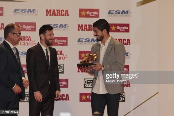 Barcelona's Argentinian striker Lionel Messi receives his fourth Golden Boot trophy trophy from his Uruguayan teammate Luis Suarez as top scorer in...
