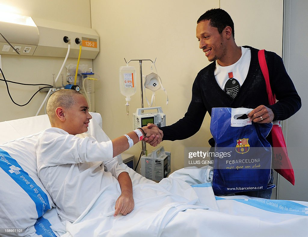 Barcelona's Brazilian defender Adriano (R) shakes hands with Joan during a visit at the Hospital Vall d'Hebron in Barcelona on January 4, 2013.