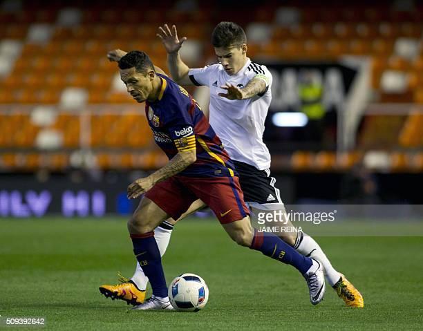 Barcelona's Brazilian defender Adriano vies with Valencias forward Santi Mina during the Spanish Copa del Rey football match Valencia CF vs FC...