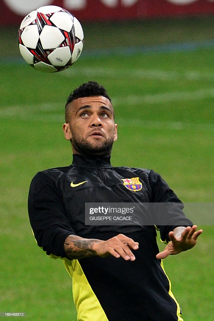 Barcelona's Brazilian defender Dani Alves attends a training session, on the eve of Champions League football match between AC Milan and FC Barcelona, on October 21, 2013 at the San Siro Stadium in Milan. AFP PHOTO / GIUSEPPE CACACE