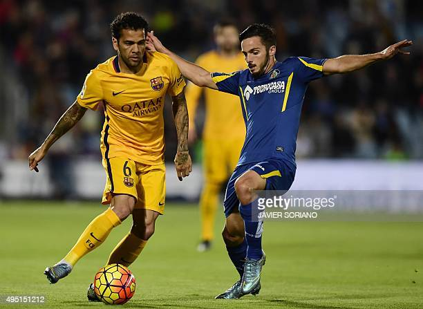 Barcelona's Brazilian defender Dani Alves vies with Getafe's midfielder Victor Rodriguez during the Spanish league football match Getafe CF vs FC...