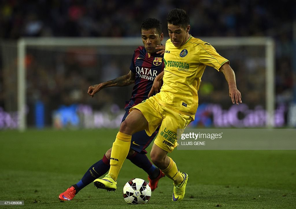Barcelona's Brazilian defender <a gi-track='captionPersonalityLinkClicked' href=/galleries/search?phrase=Dani+Alves&family=editorial&specificpeople=2191863 ng-click='$event.stopPropagation()'>Dani Alves</a> (L) vies with Getafe's Uruguayan defender Emiliano Velazquez (R) during the Spanish league football match FC Barcelona vs Getafe at the Camp Nou stadium in Barcelona on April 28, 2015.