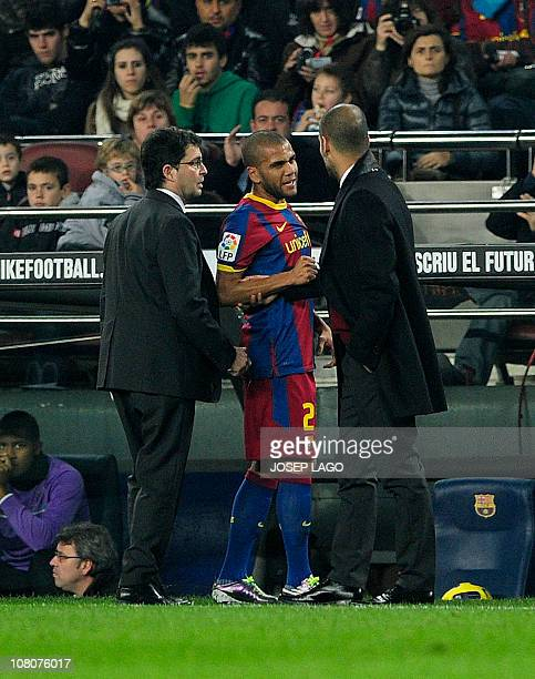 Barcelona's Brazilian defender Daniel Alves chats with Barcelona's coach Josep Guardiola as he leaves the pitch after being injured during the...