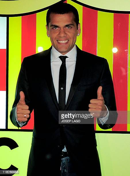 Barcelona's Brazilian defender Daniel Alves gives a thumbs up on March 23 2011 at Camp Nou stadium in Barcelona after signing his threeyear contract...