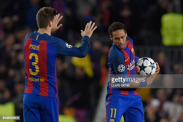 Barcelona's Brazilian forward Neymar and Barcelona's defender Gerard Pique celebrate Paris SaintGermain's own goal during the UEFA Champions League...