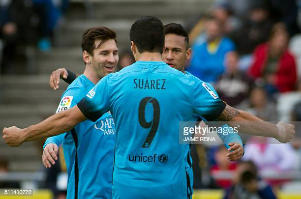 Barcelona's Brazilian forward Neymar celebrates a goal with Barcelona's Argentinian forward Lionel Messi and Barcelona's Uruguayan forward Luis...