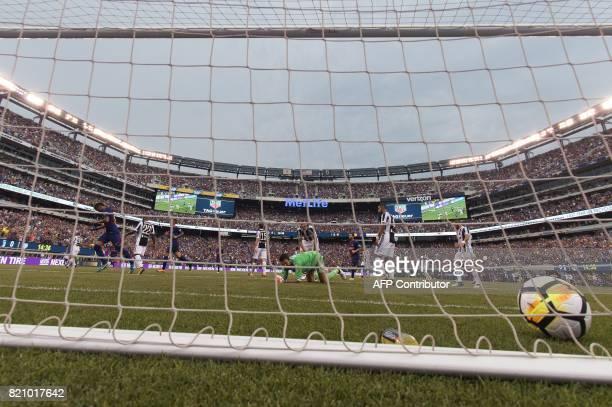 Barcelona's Brazilian forward Neymar celebrates after scoring as Juventus' goalkeeper from Italy Gianluigi Buffon looks on during the International...