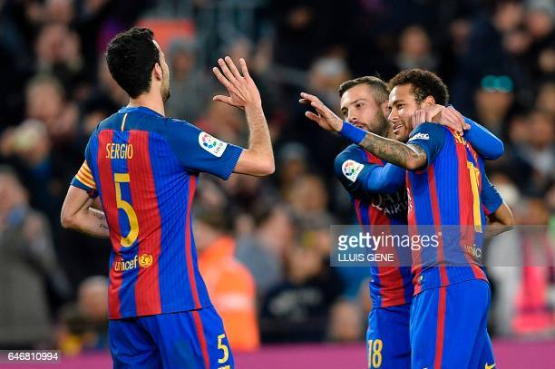 Barcelona's Brazilian forward Neymar celebrates with Barcelona's defender Jordi Alba and Barcelona's midfielder Sergio Busquets after scoring during...