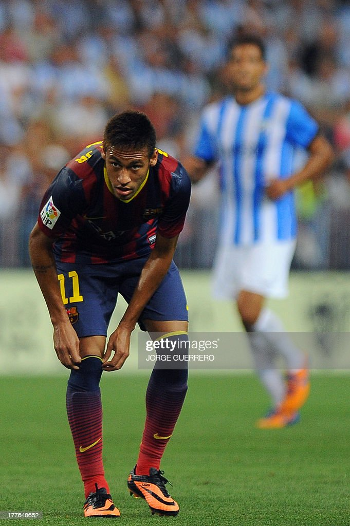 Barcelona's Brazilian forward Neymar da Silva Santos adjusts his sock during the Spanish league football match Malaga CF vs FC Barcelona at Rosaleda stadium in Malaga on August 25, 2013.