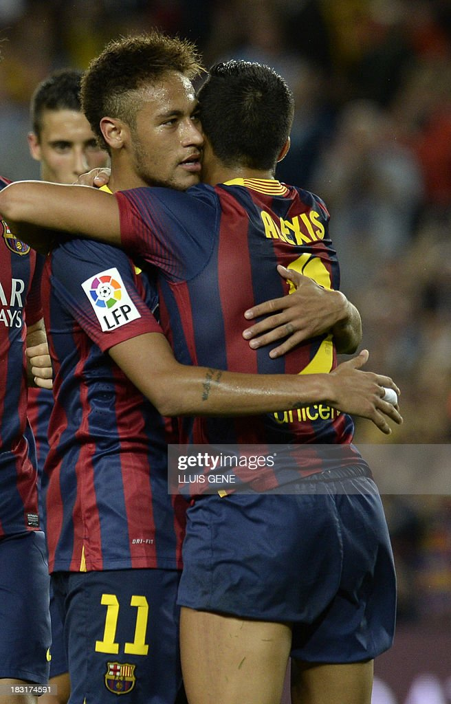 Barcelona's Brazilian forward Neymar da Silva Santos (L) celebrates with Barcelona's Chilean forward Alexis Sanchez after scoring during the Spanish league football match FC Barcelona vs Real Valladolid CF at the Camp Nou stadium in Barcelona on October 5, 2013. AFP PHOTO / LLUIS GENE