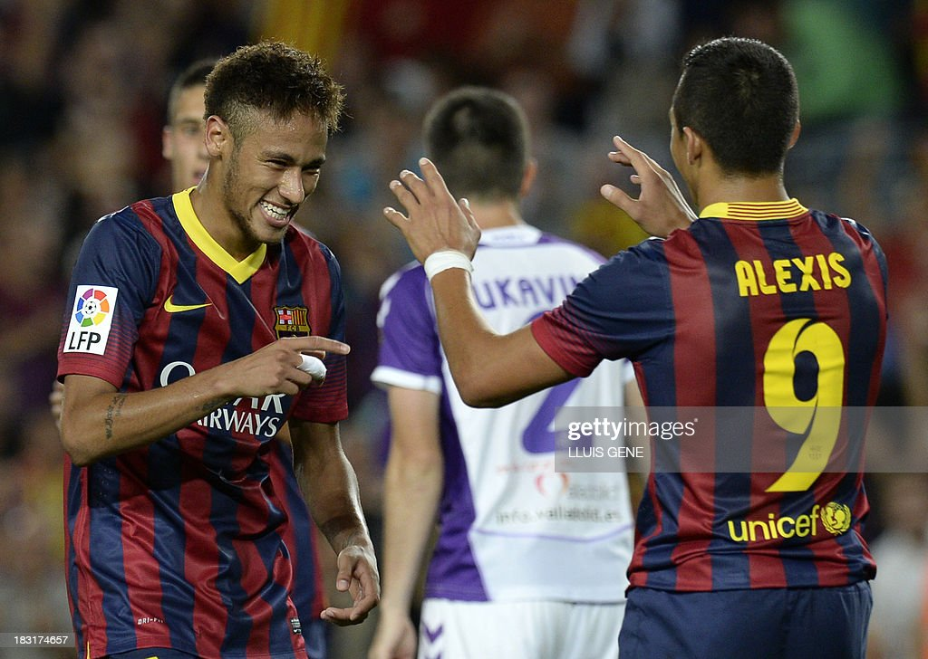 Barcelona's Brazilian forward Neymar da Silva Santos (L) celebrates with his teammate Chilean forward Alexis Sanchez after scoring during the Spanish league football match FC Barcelona vs Real Valladolid CF at the Camp Nou stadium in Barcelona on October 5, 2013. AFP PHOTO / LLUIS GENE