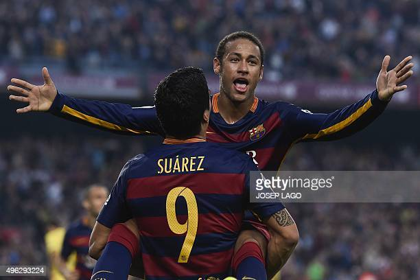 Barcelona's Brazilian forward Neymar da Silva Santos Junior is congratulated by his teammate Barcelona's Uruguayan forward Luis Suarez after scoring...