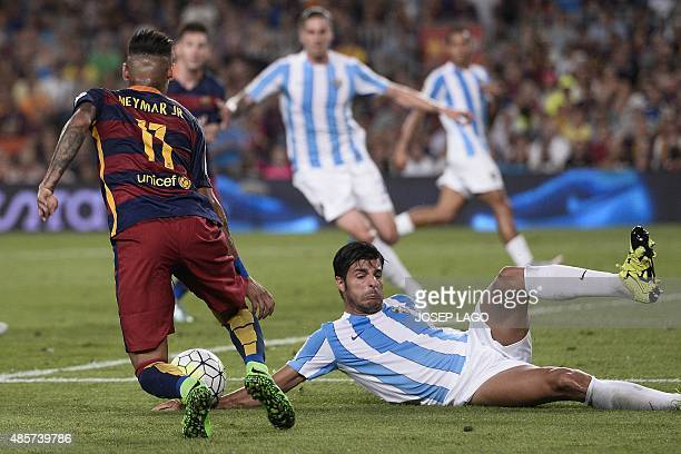 Barcelona's Brazilian forward Neymar da Silva Santos Junior vies with Malaga's defender Miguel Torres during the Spanish league football match FC...